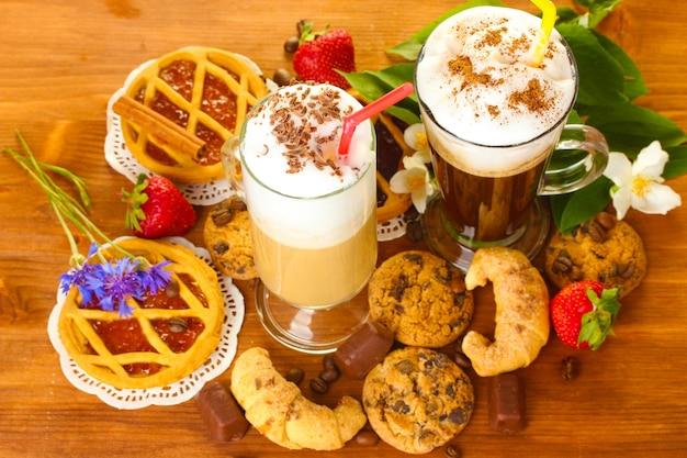 Glazen koffiecocktail op houten tafel met snoep en bloemen