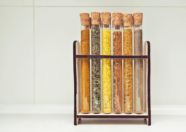 Glazen kolven met verschillende soorten kruiden op de keukentafel