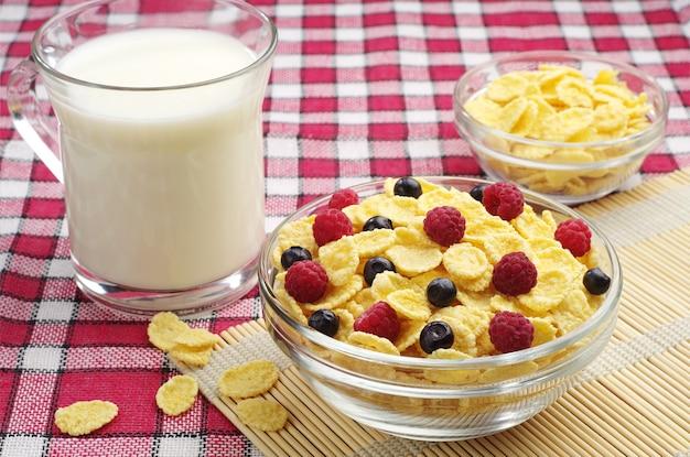 Glazen kom cornflakes met bessen en kopje melk op een rood tafellaken