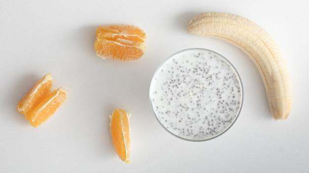 Glazen kom met chia yoghurt banaan en mandarijn plakjes op een witte achtergrond. bovenaanzicht.