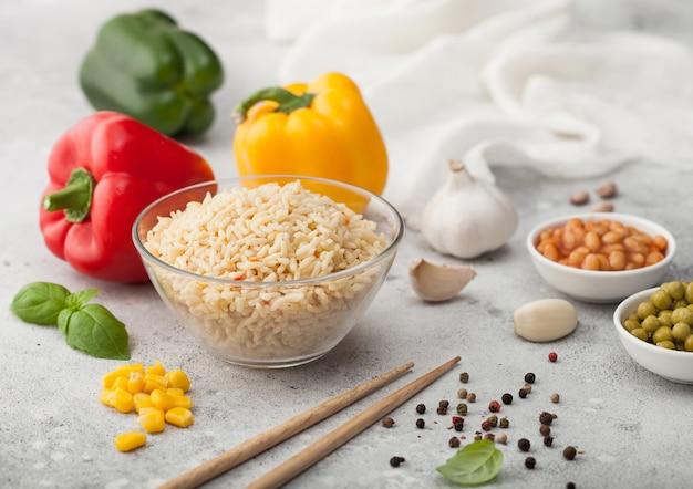 Glazen kom met gekookte langkorrelige basmatirijst met groenten op lichte achtergrond met stokken en paprikapeper met maïs, bonen en erwten.