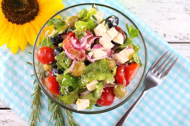 Glazen kom met griekse salade geserveerd op servet op houten oppervlak