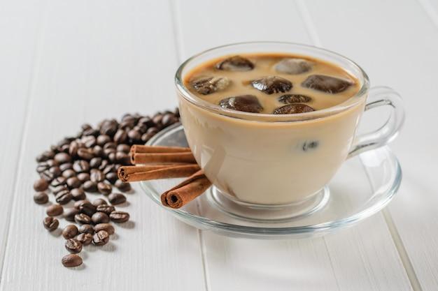 Glazen kom met ijskoffie, kaneelstokjes en verspreide koffiebonen op witte tafel. verfrissende en verkwikkende drank van koffiebonen en melk.
