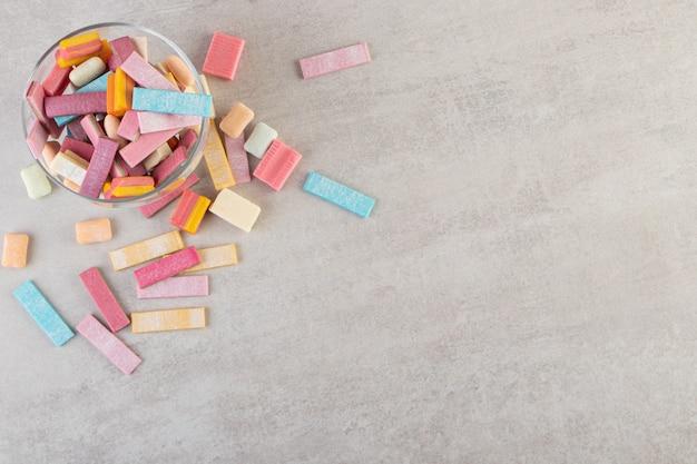 Glazen kom met kleurrijke kauwgom stenen tafel.