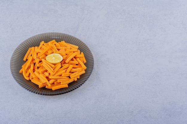 Glazen kom met knapperige chips op stenen tafel.