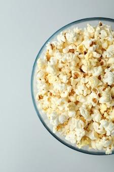 Glazen kom met popcorn op lichtgrijze achtergrond.