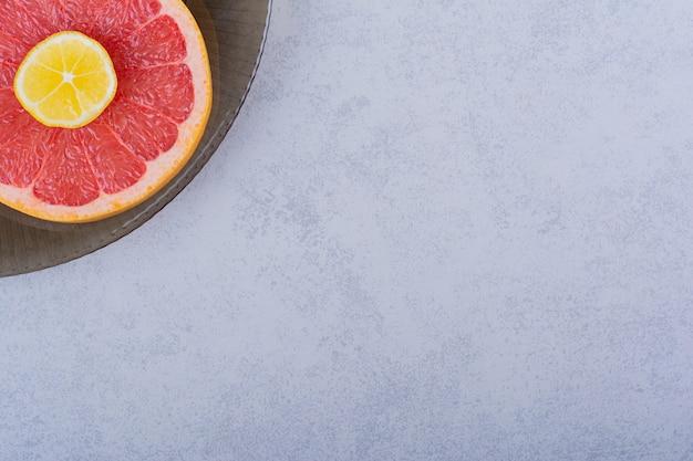 Glazen kom verse grapefruitschijfje met citroen op steen.