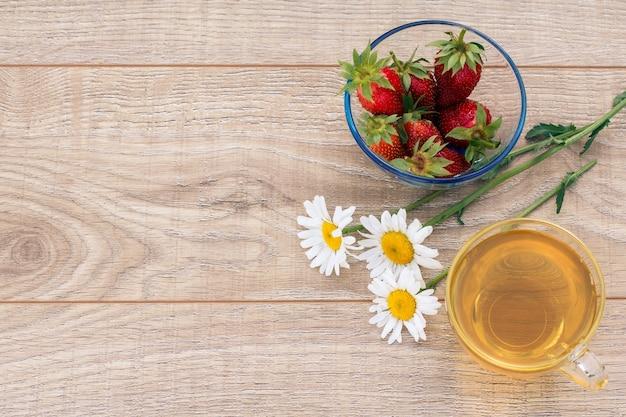 Glazen kopje groene thee, kamille bloemen, glazen kom met verse aardbeien op de houten planken. bovenaanzicht.
