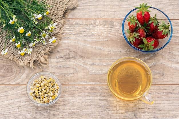 Glazen kopje groene thee, kamille bloemen, glazen kommen met droge bloemen van matricaria chamomilla en verse aardbeien op de houten achtergrond. bovenaanzicht.