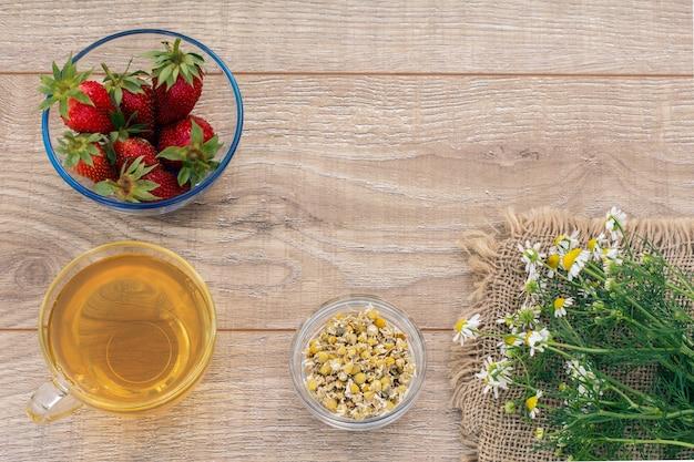 Glazen kopje groene thee, kamille bloemen, glazen kommen met droge bloemen van matricaria chamomilla en verse aardbeien op de houten planken. bovenaanzicht.