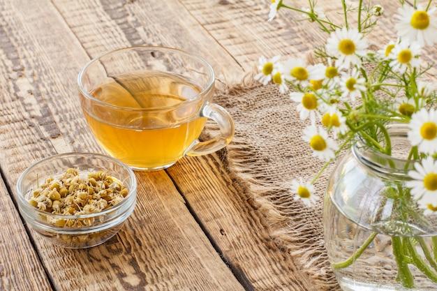 Glazen kopje groene thee, kleine glazen kom met droge bloemen van matricaria chamomilla en verse witte kamille bloemen op zak en houten achtergrond.