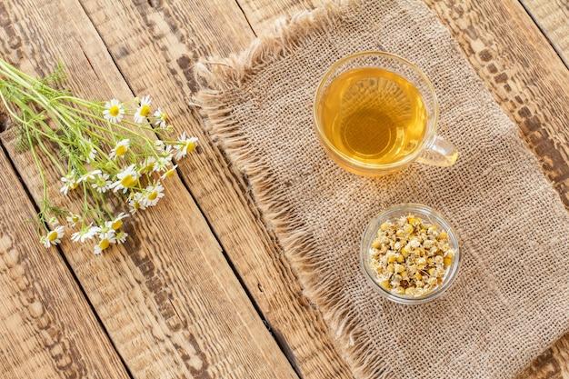 Glazen kopje groene thee, kleine glazen kom met droge bloemen van matricaria chamomilla op zak en verse witte kamille bloemen op houten achtergrond. bovenaanzicht.