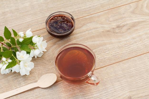Glazen kopje groene thee, zelfgemaakte aardbeienjam in een glazen kom en witte jasmijn bloemen op houten achtergrond. bovenaanzicht met kopie op afstand.