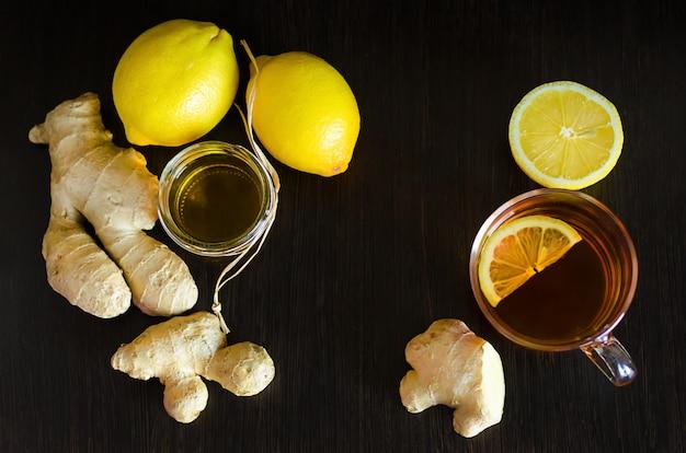 Glazen kopje hete thee, gezonde drank met honing, citroen, gember op donkere houten. antioxidant, stimuleert het immuunsysteem