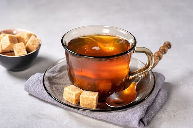 Glazen kopje hete zwarte thee met suikerklontjes op lichte achtergrond
