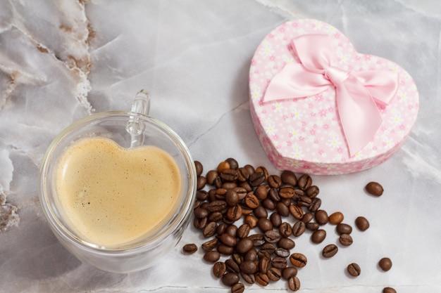 Glazen kopje koffie en een geschenkdoos met gebrande koffiebonen op de keukentafel. de beker en de doos in de vorm van een hart. bovenaanzicht.