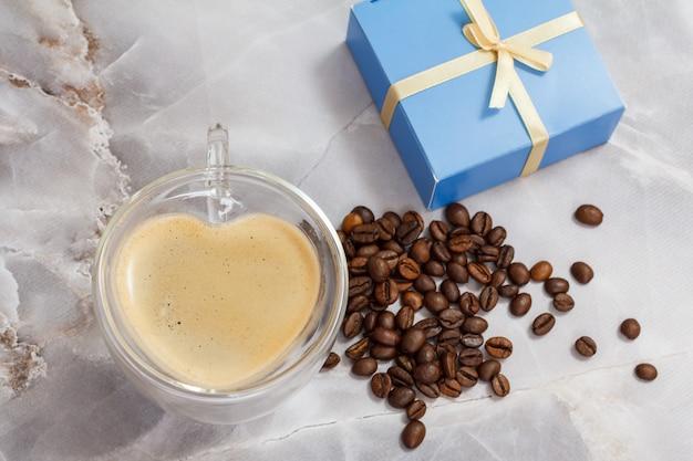 Glazen kopje koffie in de vorm van een hart, gebrande koffiebonen en een geschenkdoos op de keukentafel.