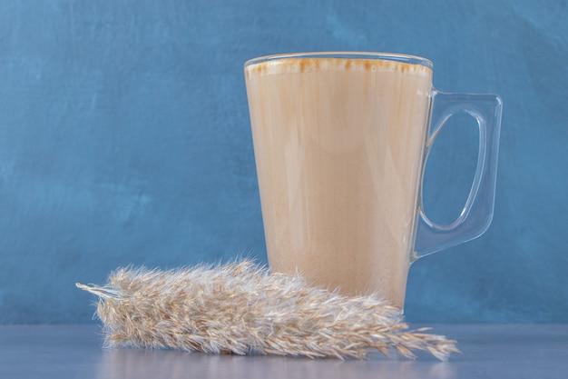 Glazen kopje koffie latte naast pampagras, op de blauwe tafel.