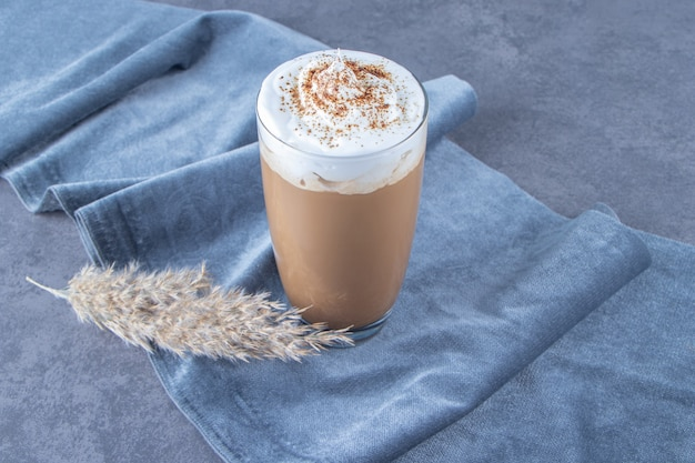 Glazen kopje koffie latte op stuk stof naast pampagras, op de blauwe achtergrond.