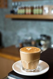 Glazen kopje latte met latte kunst in de cafetaria