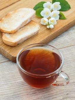 Glazen kopje thee, brood en witte jasmijn bloemen op houten snijplank. bovenaanzicht.