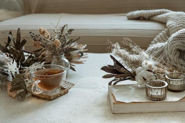 Glazen kopje thee, gebreid element en gedroogde bloemen in het interieur van de kamer
