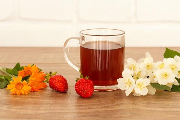 Glazen kopje thee met aardbeien, gele goudsbloem bloemen en witte jasmijn bloemen op houten bureaublad.