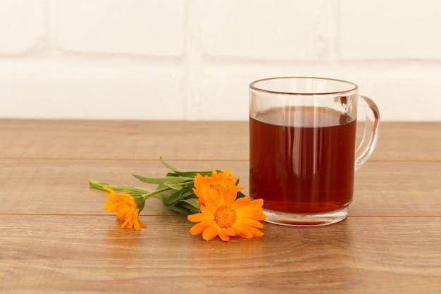 Glazen kopje thee met gele goudsbloem bloemen op houten bureaublad.