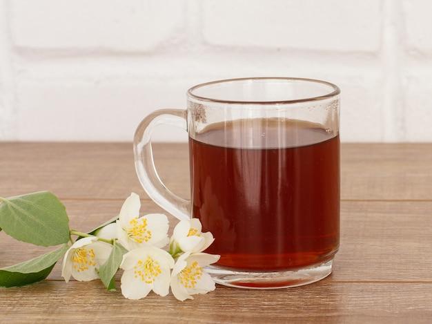Glazen kopje thee met witte jasmijn bloemen op houten bureaublad.