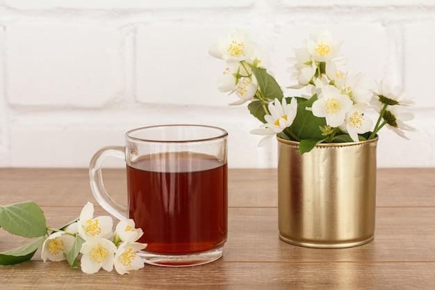 Glazen kopje thee met witte jasmijnbloemen