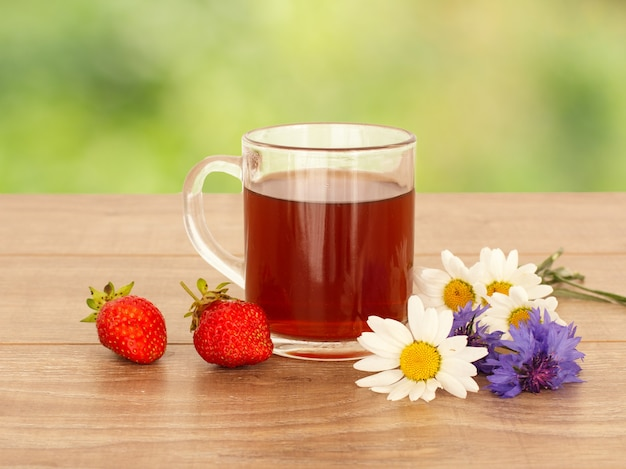 Glazen kopje thee met witte kamille bloemen