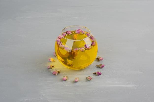 Glazen kopje thee op grijze tafel