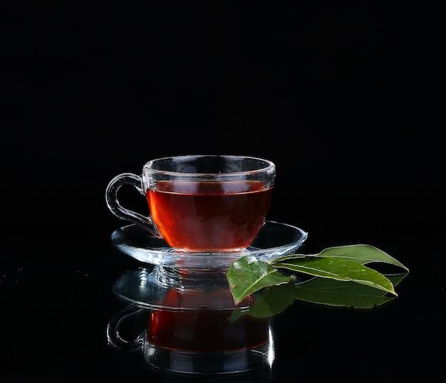 Glazen kopje thee op zwarte achtergrond.