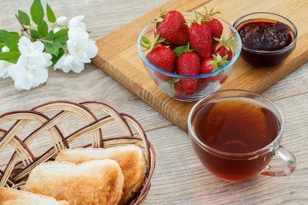 Glazen kopje thee, verse aardbeien, zelfgemaakte aardbeienjam op houten snijplank, toast in rieten mand en witte jasmijn bloemen op houten achtergrond. bovenaanzicht.