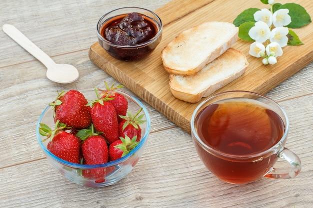 Glazen kopje thee, zelfgemaakte aardbeienjam, brood op houten snijplank en verse aardbeien, lepel en witte jasmijn bloemen op houten achtergrond. bovenaanzicht.