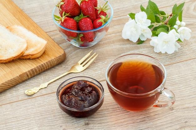 Glazen kopje thee, zelfgemaakte aardbeienjam, brood op houten snijplank en verse aardbeien, vork en witte jasmijn bloemen op houten achtergrond. bovenaanzicht.