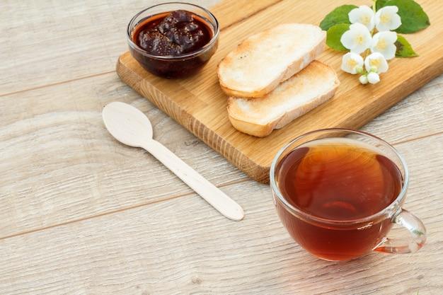 Glazen kopje thee, zelfgemaakte aardbeienjam in een kom, brood en witte jasmijn bloemen op houten snijplank, lepel op houten achtergrond. bovenaanzicht.
