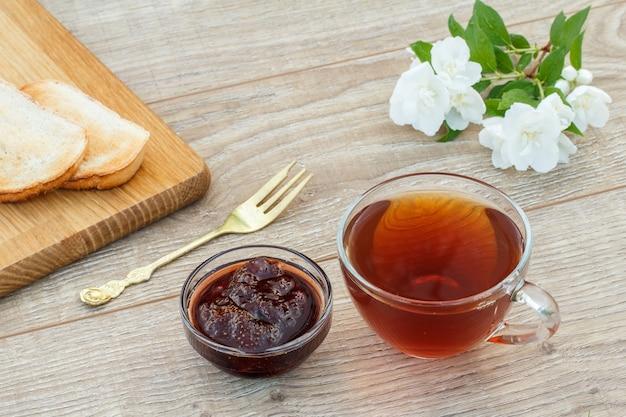 Glazen kopje thee, zelfgemaakte aardbeienjam in een kom, brood op houten snijplank, vork en witte jasmijn bloemen op houten achtergrond. bovenaanzicht.