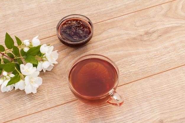 Glazen kopje thee, zelfgemaakte aardbeienjam in een kom en witte jasmijn bloemen op houten achtergrond. bovenaanzicht met kopie op afstand.