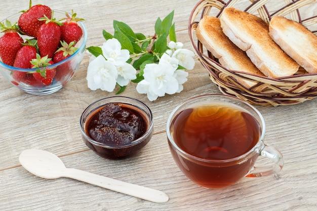 Glazen kopje thee, zelfgemaakte aardbeienjam, verse aardbeien, lepel, toast in rieten mand en witte jasmijn bloemen op houten achtergrond. bovenaanzicht.