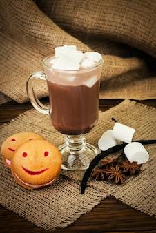 Glazen kopje warme chocolademelk met marshmallows en koekjes