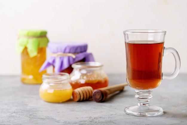 Glazen kopje zwarte thee geserveerd met honing