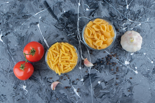 Glazen kopjes ongekookte pasta met twee verse tomaten en knoflook op een marmeren ondergrond.
