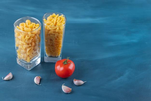 Glazen kopjes ongekookte pasta met verse rode tomaat en knoflook.