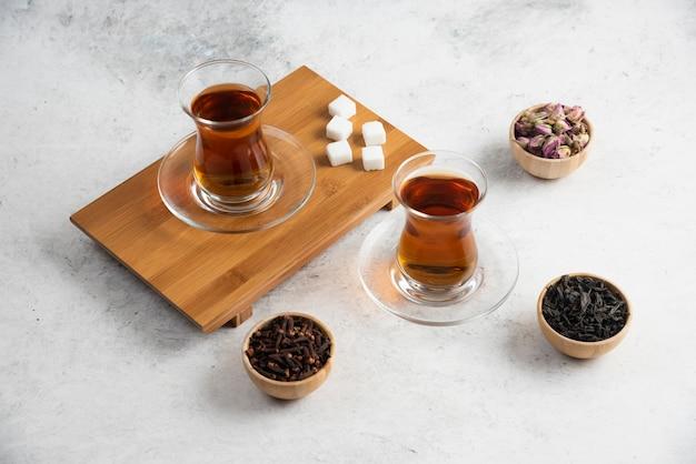Glazen kopjes thee met suiker op een houten bord.
