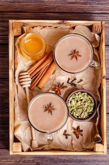 Glazen kopjes traditionele indiase thee masala thee op een dienblad met ingrediënten