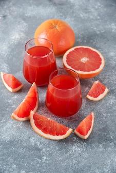 Glazen kopjes vers grapefruitsap met plakjes fruit op een houten bord.