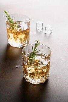 Glazen koude whisky met takjes rozemarijn