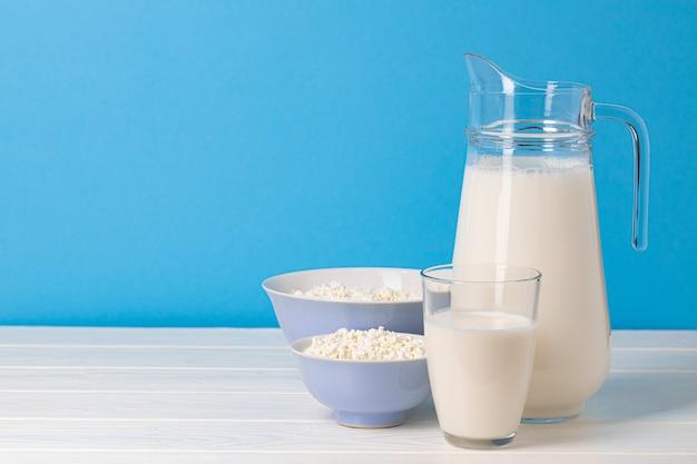 Glazen kruik melk en kom kwark op houten tafel close-up