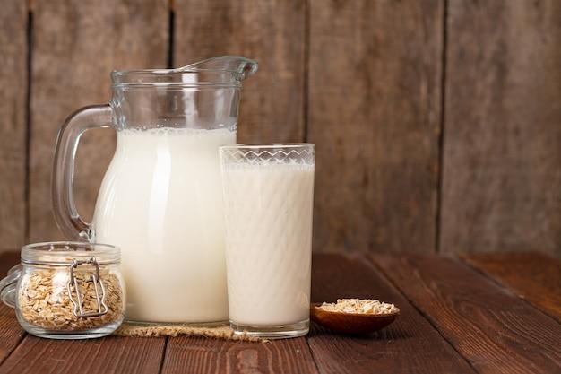 Glazen kruik melk op oude houten tafel close-up